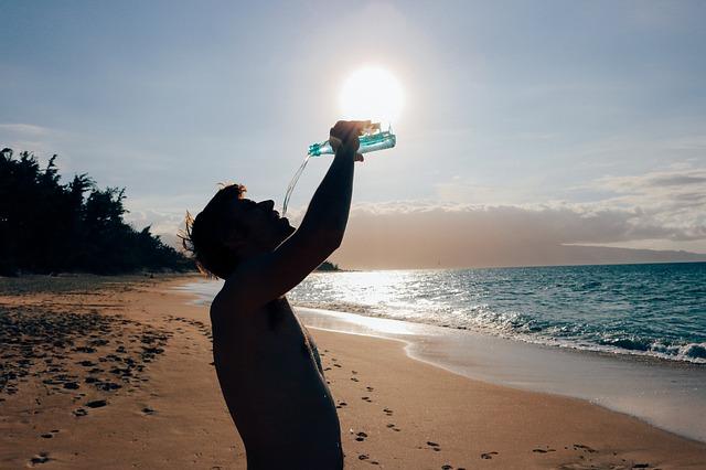 hombre bebiendo agua para cuidar pelo en verano